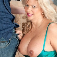Experienced fair-haired lady Miss Deb pulls out her big funbags from her lingerie on a couch