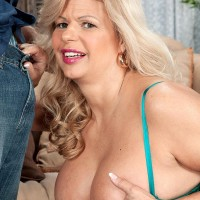 Senior yellow-haired doll Miss Deb extracts her giant boobs from her lingerie on a couch