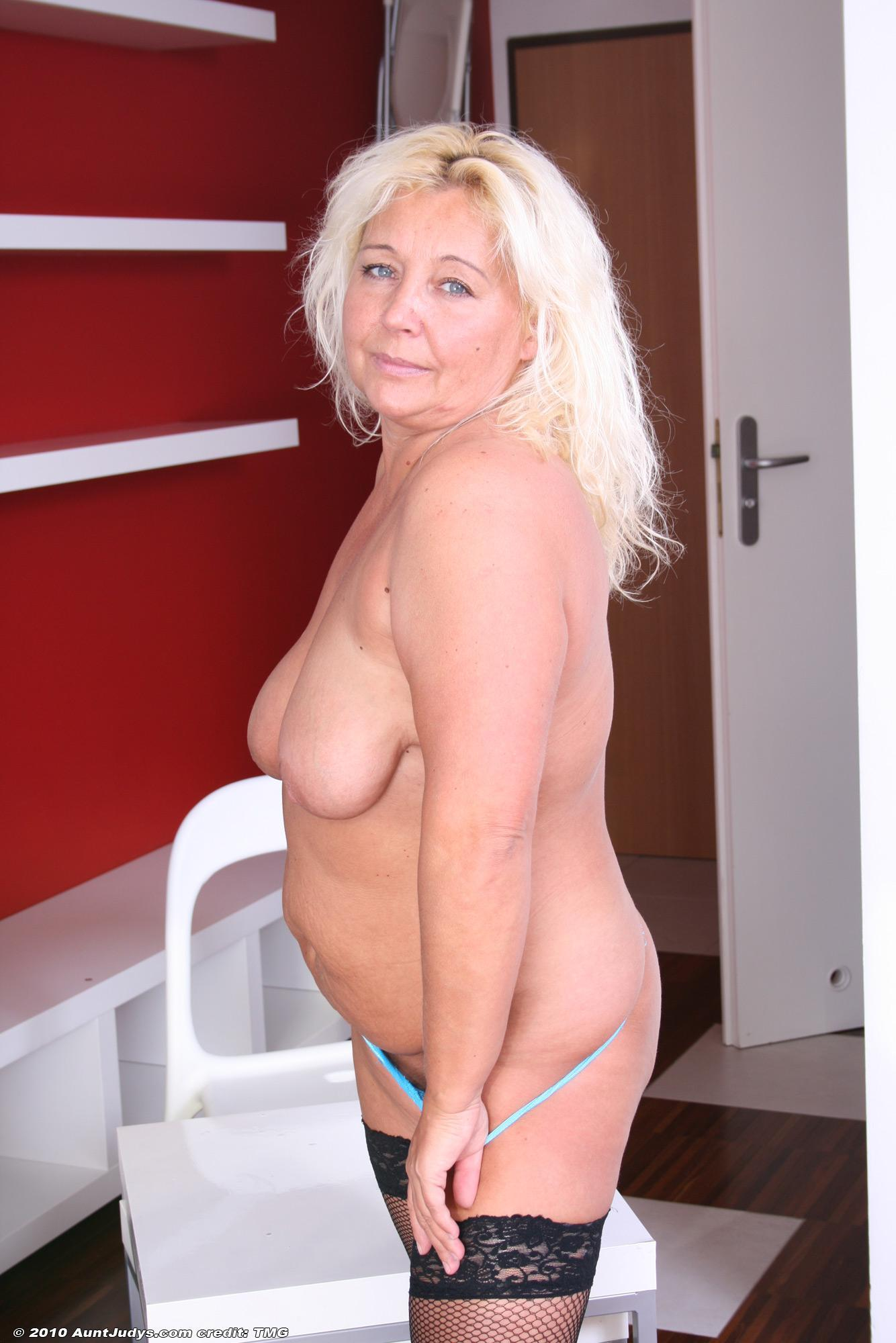 Aged yellow-haired dame doing away with skirt and melon-holder before sliding panties over monster-sized butt