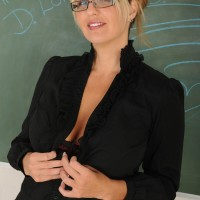 Expert blonde broad attired glasses strips nude in front of chalkboard in classroom