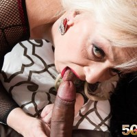 Senior platinum-blonde doll Heidi strokes and tongues a giant ebony penis in a body-stocking