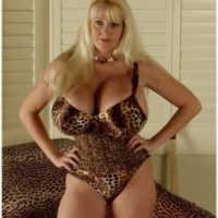 Older fair-haired lady Kayla Kleevage sets her enlargened breasts and pubic hair free on a chesterfield