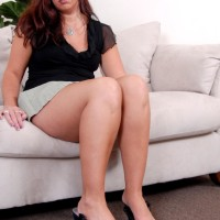 Experienced dark-haired dame doing slow striptease while taking off miniskirt and high heeled shoes