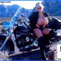 Mature model Kayla Kleevage puts her humungous boobies on demonstrate in leather by a motorcycle