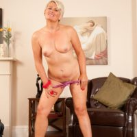 Senior platinum ash-blonde extracts her flat chest as she strips to high heels on a leather tabouret