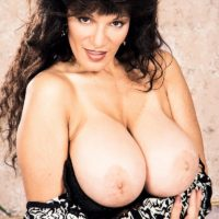 Mature adult film starlet Busty BriAnna sets her hefty breasts free and her smooth-shaven vagina as well