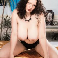 Older X-rated film star Olga extracts her big titties before revealing her bush in solo act