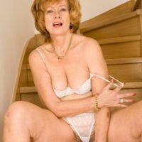 Elderly redhead doffs a dress and pretties to pose downright nude on wooden stairs