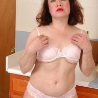 Mature ginger-haired strips off translucent attire and lingerie to pose naked in kitchen