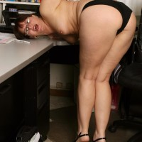 Older assistant makes her naked posing debut while at work during solo activity