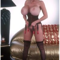 Elder solo model Kayla Kleevage demonstrates her hefty fake titties in a midbody cincher