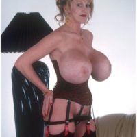 Senior solo model Kayla Kleevage showcases her immense fake breasts in a waist cincher