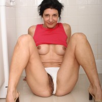 Aged doll strips nude in the kitchen before taking a banana to her wooly cooch