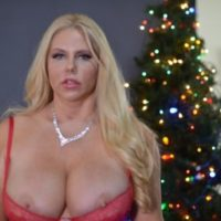 Middle-aged golden-haired Karen Fisher lets a nipple slip loose of lingerie at X-mas time