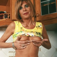 Middle expert housewife takes off denim jeans and underwear to model naked in kitchen