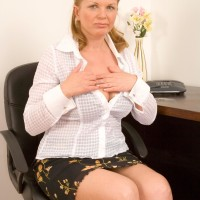 Middle senior doll removing skirt and lingerie to model nude at office desk