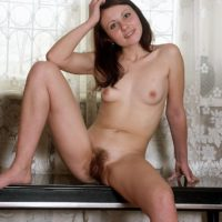 Nude amateur brown-haired solo female demonstrating furry muff in bare feet on bench