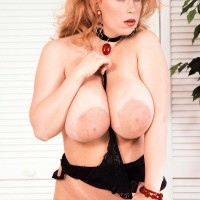 All natural ginger-haired Tabatha Towers plays with her gigantic titties in a choker and hose