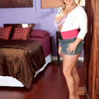 Fully clothed light-haired babe Anastasia Blake showing off bosom in denim mini-skirt