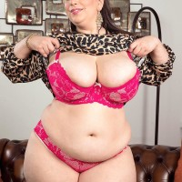 Plus-size solo chick Mia Hotty stripping down to pinkish bra and panty set on chesterfield