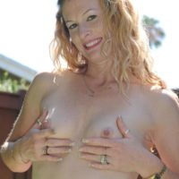 Old amateur gal removes swimsuit to pose naked outdoors in back yard