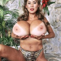 Mature Asian woman Minka flashes her humungous titties before loosing her trimmed cootchie
