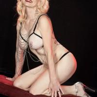 Elder light-haired Cammille Austin wears nip clips while posing translucent lingerie