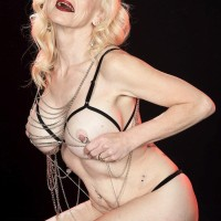 Elder light-haired Cammille Austin wears nip clips while posing translucent lingerie