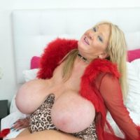 Elderly golden-haired Kayla Kleevage munches a nipple while playing with her enlargened tits