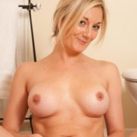 Older platinum-blonde solo model undressing nude to pose naked in the washroom