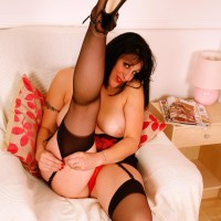 Experienced black-haired solo model exposing big juggs and plus-size booty in ebony nylons and high-heeled shoes