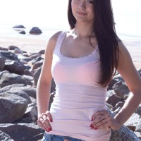 Puny black-haired first-timer Olivia displaying perky teen tits outdoors on rocky beach