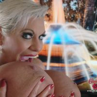 Platinum golden-haired lady Claudia Marie holds her giant boobies while sucking on a nipple
