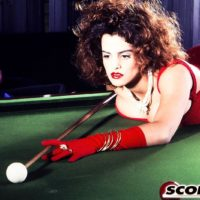 Pornostar Nilli Willis unsheathes her immense juggs on pool table in red gloves and dress