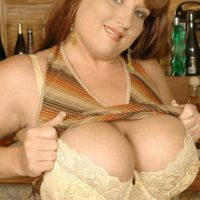 Red-haired solo female Brandy Dean unleashing large tits in denim mini-skirt and high heels