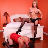 Red-haired mistress Nikki Delano boinks her sissy man in the butt with a strap on cock in pantyhose