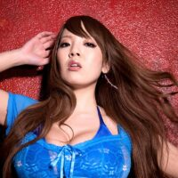 Redheaded Asian stunner Hitomi sets her gigantic titties free whiel disrobing