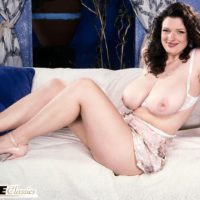 Solo chick Olga sports curly hair while setting her fine boobies loose on top of her bed
