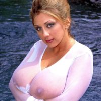 Solo model Autumn Jade demonstrates off her huge breasts in a assets of water in semi-transparent garment