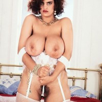 Solo model Nilli Willis seizes her enormous boobs in milky nylons and garters