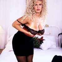 Solo model Taylor Marie holds her giant funbags in a waistline cincher and garters with hosiery