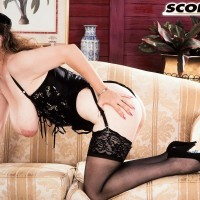 Solo model Traci Burr holds her hefty boobies in ebony lingerie and tights with high heels