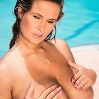 Solo model Trinity Loren shows off her large boobs while taking a dip in the pool