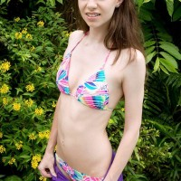 Seductive teenage female Tali Dova unleashes her smallish boobies from her swimsuit out by the pool