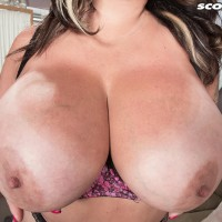 Tatted brown-haired MILF Amaya May lets out her hefty tits from her bra in a mini-skirt