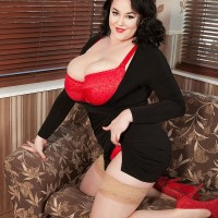 Plumper dark-haired solo model Lila Payne poses in a red melon-holder and tan hosiery on couch