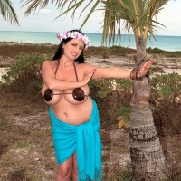 Thick female Arianna Sinn uncups her melons as she gets naked by a tropical tree