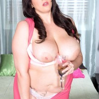 Chubber model Angel DeLuca sets her gigantic titties loose of a pinkish sundress and boulder-holder in a bedroom