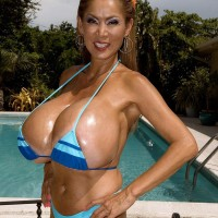 Top heavy Chinese babe Minka greasing big bathing suit garmented hooters outdoors by pool