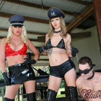 Two mistresses in hats and lengthy boots lead masculine slave by a leash